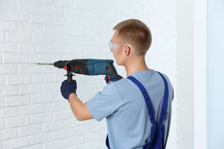 Handsome young working man using rotary hammer indoors. Home repair 写真素材