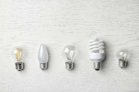 Set of different lamp bulbs on white wooden background, top view