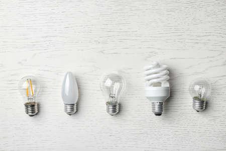 Conjunto de diferentes bombillas sobre fondo blanco de madera, vista superior Foto de archivo