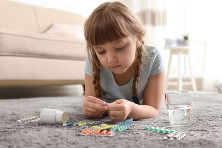 Little child with many different pills on floor at home. Danger of medicament intoxication Imagens