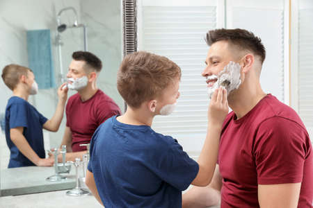 Son applying shaving foam on dads face at mirror in bathroom