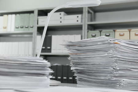 Stacks of documents on table in office
