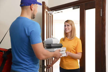 Woman receiving order from courier at door. Food delivery service Stock Photo