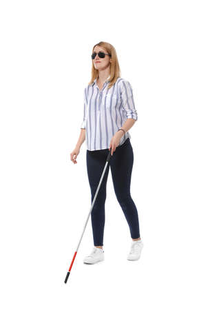 Blind woman in dark glasses with walking cane on white background