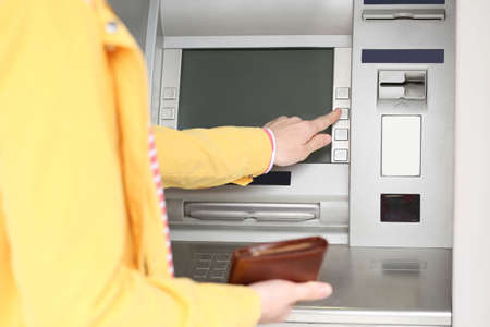 Woman using cash machine for money withdrawal outdoors, closeup