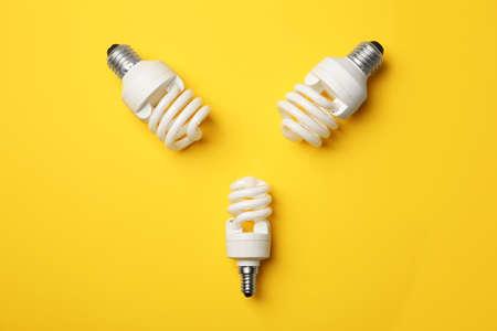 New fluorescent lamp bulbs on yellow background, top view Standard-Bild