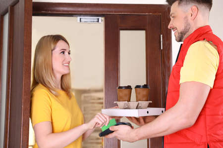 Woman paying for food delivery with credit card at door