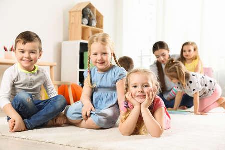 Verspielte kleine Kinder, die drinnen auf dem Boden ruhen