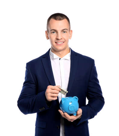 Young businessman putting money into piggy bank on white background