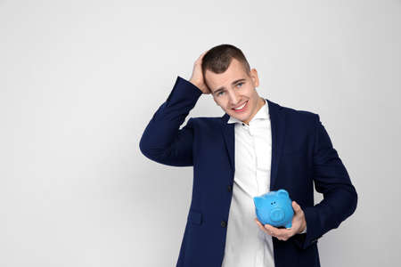 Young businessman with piggy bank on white background Banco de Imagens