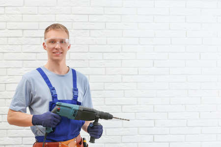 Handsome young working man with rotary hammer indoors, space for text. Home repair Imagens
