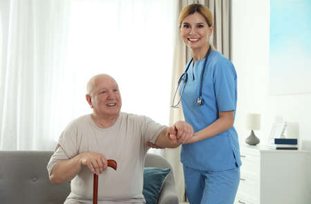 Nurse assisting elderly man with cane indoors