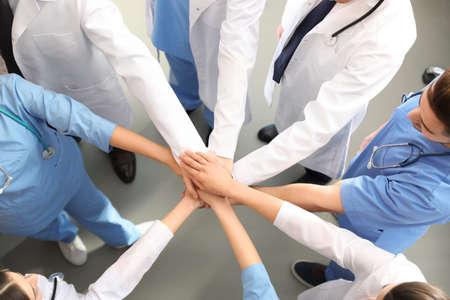 屋内で一緒に手をつないでいる医療従事者のチーム、トップビュー。ユニティコンセプト