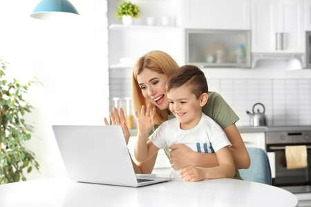 Mother and her son using video chat on laptop at table in kitchen