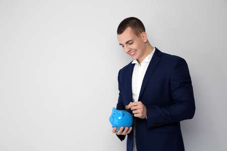 Young businessman putting coin into piggy bank on white background. Space for text
