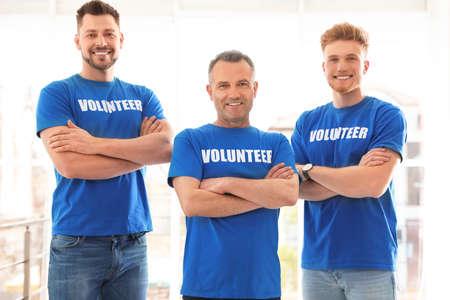 Portrait of happy male volunteers in uniform indoors