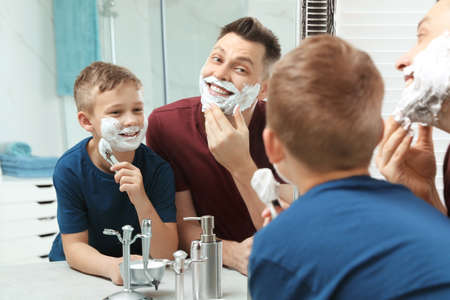 Dad and son with shaving foam at mirror