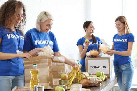 Team of volunteers collecting food donations indoors Banco de Imagens