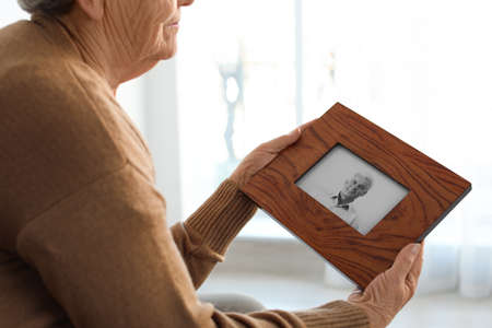 Elderly woman with framed photo of her son at home