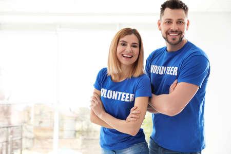 Portrait of happy volunteers in uniform indoors. Space for text