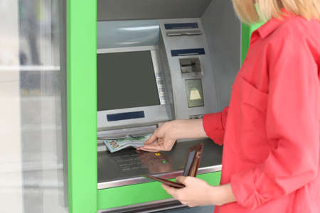 Woman taking money from cash machine outdoors, closeup Stock fotó