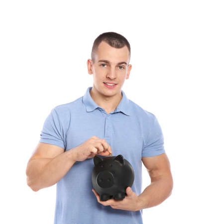 Young man putting coin into piggy bank on white background