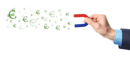 Homme attirant des symboles monétaires avec aimant sur fond blanc, gros plan