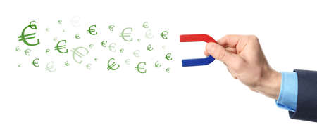 Man attracting currency symbols with magnet on white background, closeup