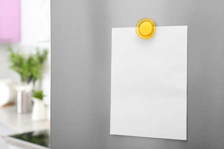Empty sheet of paper with magnet on refrigerator door in kitchen. Space for text