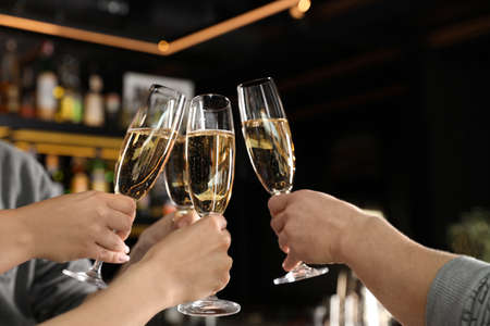 Friends clinking with glasses of champagne in bar, closeup