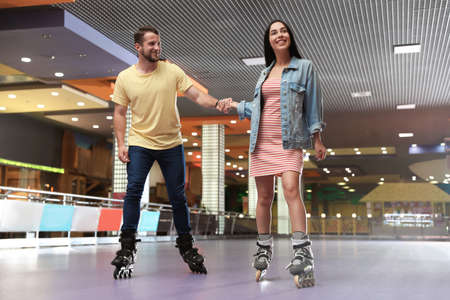 Young couple spending time at roller skating rink