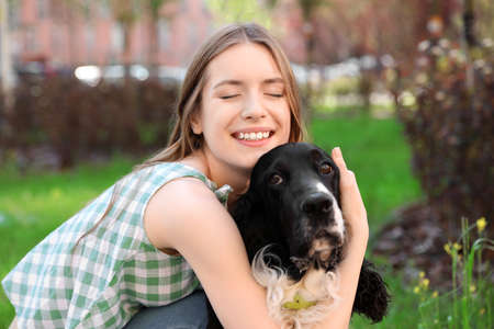 Young woman hugging her English Springer Spaniel dog outdoors