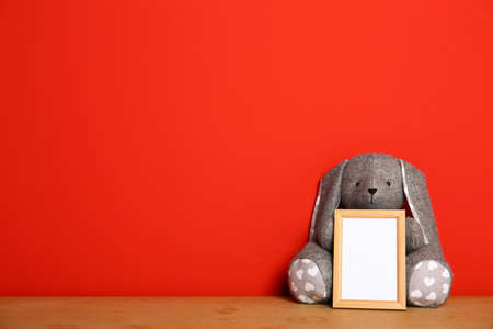 Empty photo frame and and soft rabbit on wooden table against red background, space for text. Child room interior