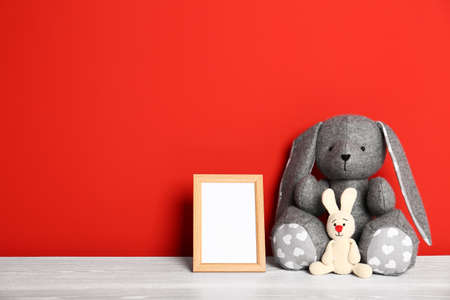 Soft toys and photo frame on table against red background, space for text. Child room interior