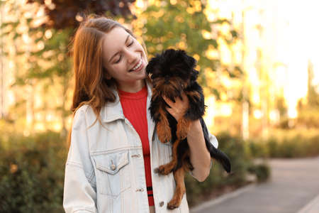 Young woman with adorable Brussels Griffon dog in park
