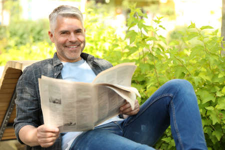 Handsome mature man with newspaper on bench in park 스톡 콘텐츠