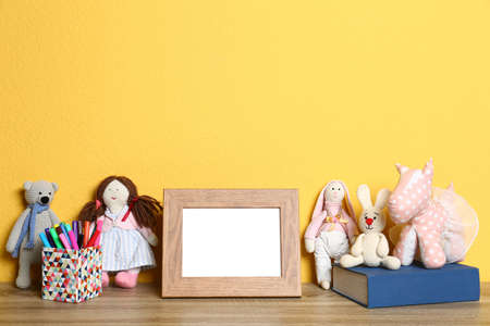 Soft toys and photo frame on table against yellow background, space for text. Child room interior