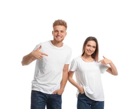 Pareja joven vistiendo camisetas en blanco aisladas en blanco. Maqueta para el diseño