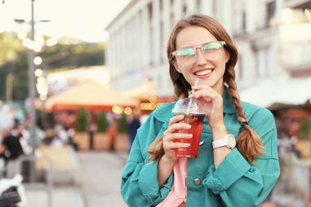 Young woman with refreshing drink on city street. Space for text 写真素材