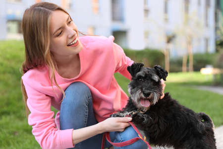 Young woman with Miniature Schnauzer dog outdoors