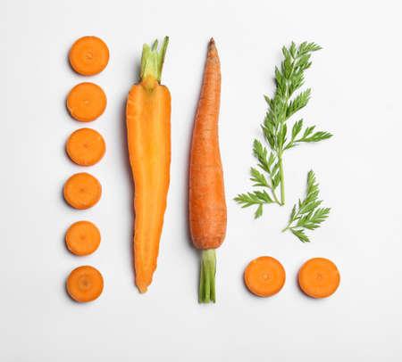 Cortar zanahorias y hojas aisladas en blanco, vista superior