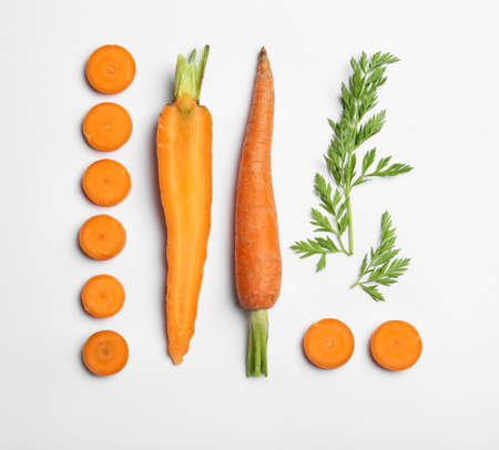Cut carrots and leaves isolated on white, top view