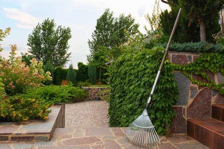 Beautiful flowerbed and rake on backyard. Home gardening Stock Photo