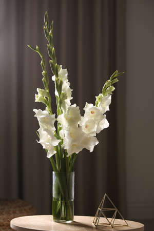 Vase with beautiful white gladiolus flowers on wooden table in room
