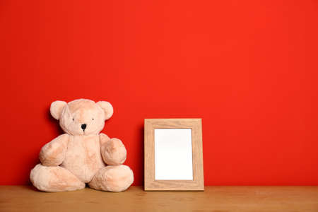 Teddy bear and photo frame on table against red background, space for text. Child room interior