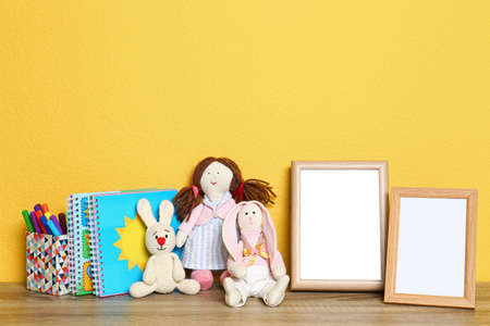 Soft toys and photo frames on table against yellow background, space for text. Child room interior Stock Photo