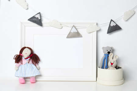 Soft toys and photo frame on table against white background, space for text. Child room interior