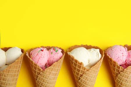 Deliciosos helados en conos de oblea sobre fondo amarillo, plano laical. Espacio para texto
