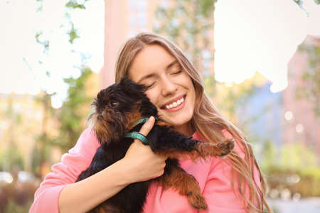 Young woman with adorable Brussels Griffon dog outdoors Imagens