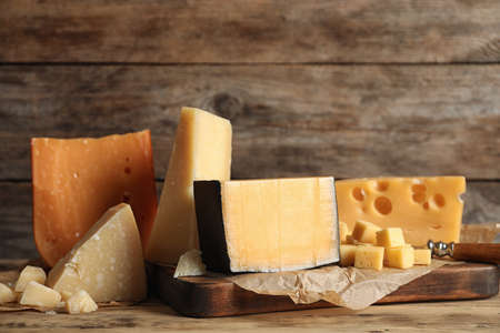Different types of delicious cheese on table against wooden background
